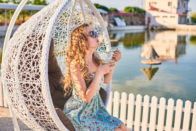 Piękna kobieta w okularach przeciwsłonecznych usiąść w białym wiszącym krześle z rattanu