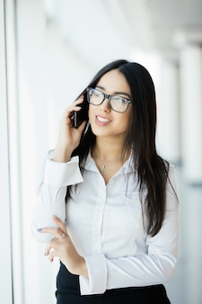Piękna kobieta w okularach rozmawia przez telefon w pobliżu panoramicznych okien.