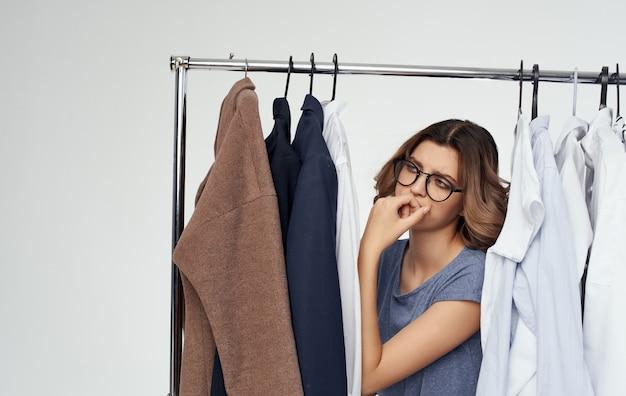 Piękna kobieta w okularach stoi w pobliżu ubrań szafa na ubrania model.