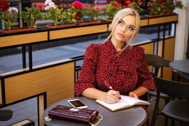 Piękna kobieta w okularach w czerwonej sukience siedzi z notatnikiem w kawiarni