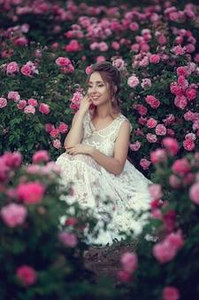 Piękna kobieta w parku kwiatowym, róże ogrodowe. makijaż, włosy, wieniec róż. długa suknia ślubna. kobieta w stylu boho
