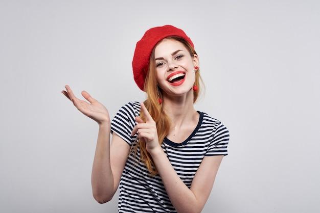 Piękna kobieta w pasiastym tshirt czerwonych ustach gest z rękami jasnym tłem