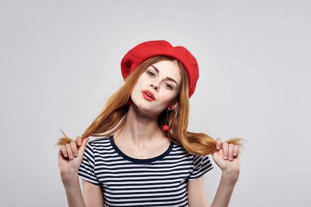 Piękna kobieta w pasiastym tshirt czerwonych ustach gest z rękami na białym tle
