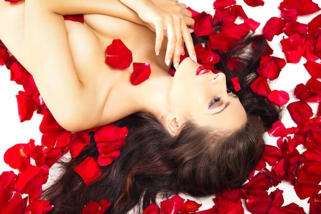 Piękna kobieta w płatkach czerwonych róż na białym