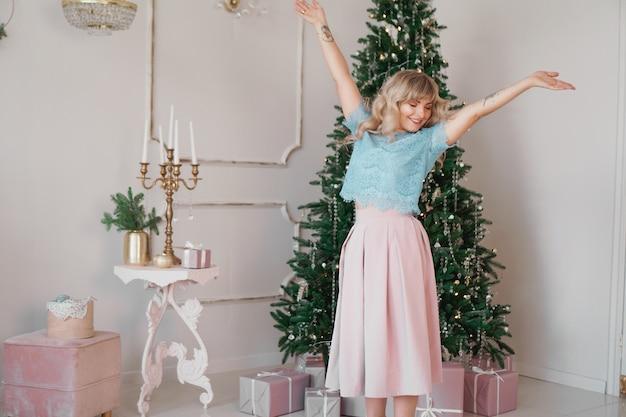 Piękna kobieta w pobliżu choinki uśmiechnięta tańczy w pięknej sukience w urządzonym domu, szczęśliwego nowego roku