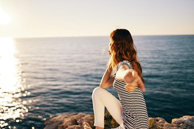 Piękna kobieta w pobliżu morza o zachodzie słońca