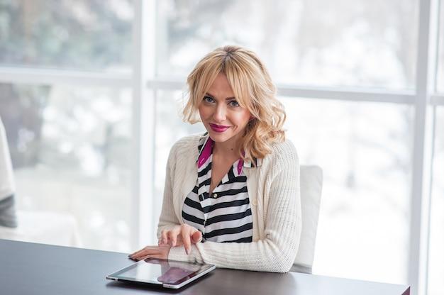Piękna kobieta w pobliżu okna z laptopem