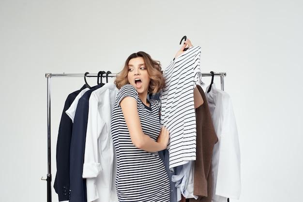 Piękna kobieta w pobliżu ubrań zakupoholiczka na białym tle