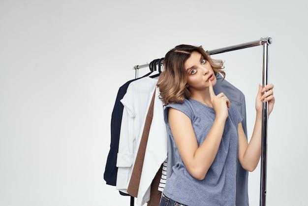 Piękna kobieta w pobliżu ubrania zakupoholiczka na białym tle. zdjęcie wysokiej jakości