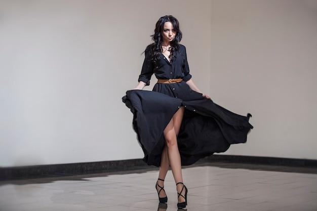 Piękna kobieta w pokoju studio tańczy w czarnej sukience z długimi ciemnymi lokami na głowie