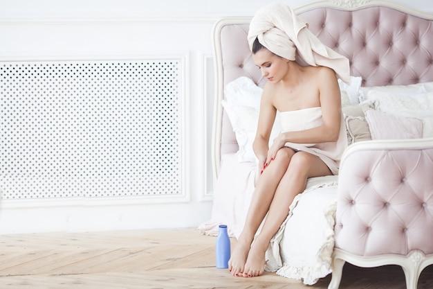 Piękna kobieta w ręczniku po kąpieli stosując balsam do ciała