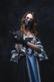Piękna kobieta w renesansowej sukience, masce na twarz i rękawiczkach, starej i nowej koncepcji