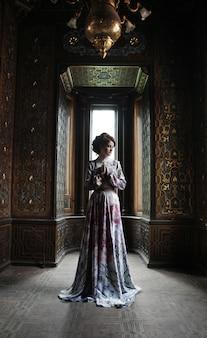 Piękna kobieta w różowej sukience pozowanie w luksusowy pałac