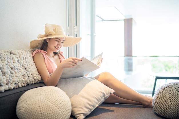 Piękna kobieta w różowym bikini siedzi i czyta książkę na wygodnym siedzeniu w pokoju.