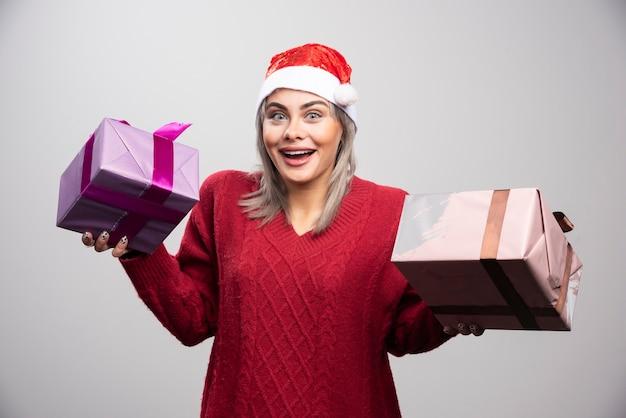 Piękna kobieta w santa kapeluszu pozuje z prezentami bożonarodzeniowymi.