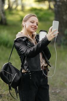Piękna kobieta w skórzanej kurtce i słuchawkach spaceruje po parku podczas rozmowy wideo z telefonu uśmiecha się i pije kawę