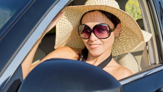 Piękna kobieta w słomkowym kapeluszu z szerokim rondem i okulary przeciwsłoneczne siedzi na siedzeniu kierowcy samochodu