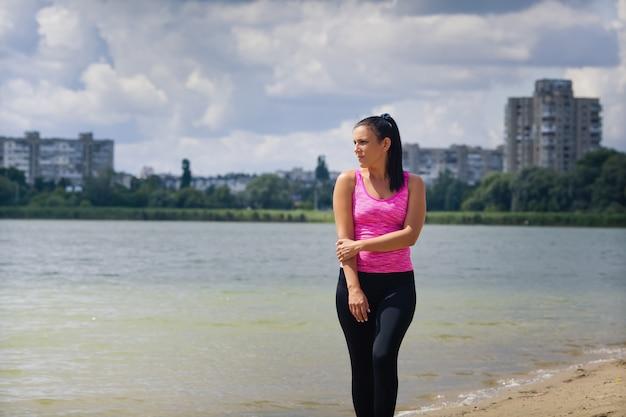 Piękna kobieta w sportowym mundurze na jeziorze w mieście