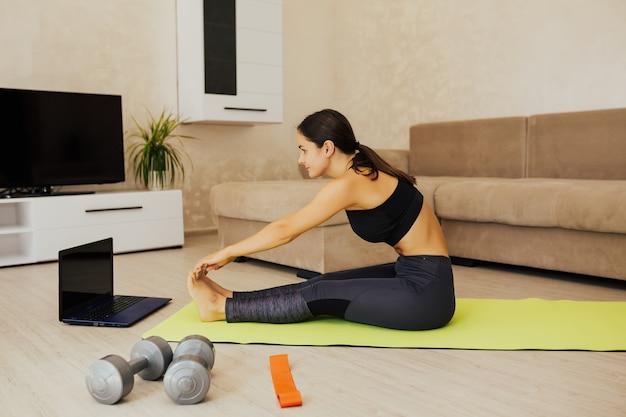 Piękna kobieta w sprawnej robi rozciąganie siedząc na podłodze na macie do jogi.