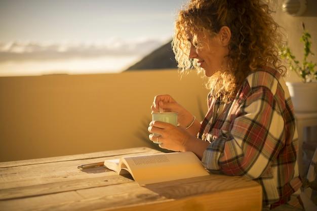 Piękna kobieta w średnim wieku czyta książkę i relaksuje się, ciesząc się wypoczynkiem w domu na tarasie