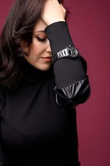 Piękna kobieta w średnim wieku na sobie czarny zegarek. strzał w nadgarstek