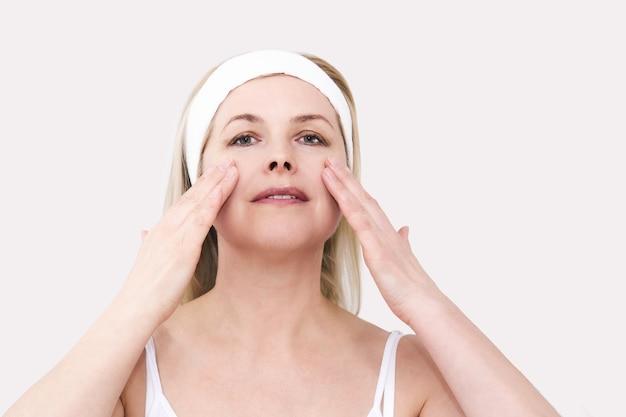 Piękna kobieta w średnim wieku robi sobie masaż twarzy, dotyka skóry palcami, portret w zbliżeniu