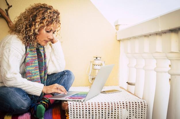 Piękna kobieta w średnim wieku siedząca na tarasie w domu, pracująca i pisząca na laptopie