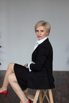 Piękna kobieta w średnim wieku siedzi na krześle