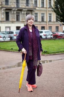 Piękna kobieta w średnim wieku stoi na ulicy w przypadkowym ubraniu z żółtym parasolem.