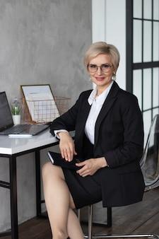 Piękna kobieta w średnim wieku ubrana w biznesowe ubrania przy stole