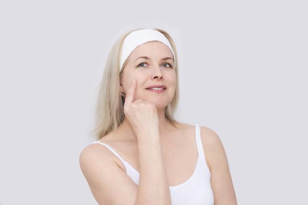 Piękna kobieta w średnim wieku w opasce do włosów do zabiegów kosmetycznych wskazuje palcem na stan skóry twarzy, portret z bliska