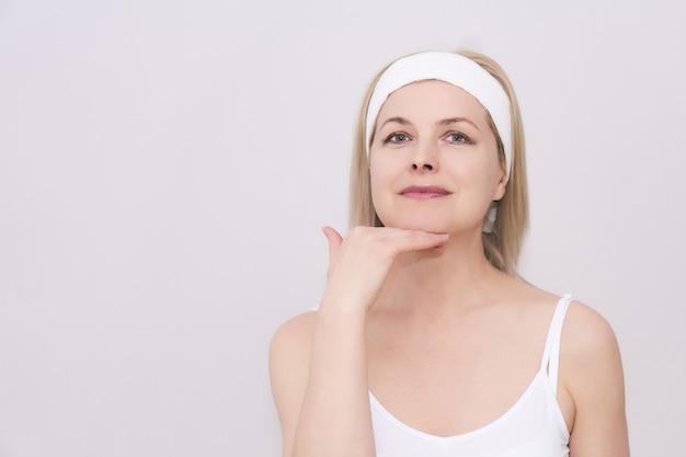 Piękna kobieta w średnim wieku wykonuje automasaż twarzy, ćwiczy, aby pozbyć się podwójnego podbródka