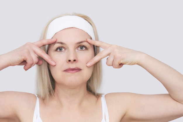 Piękna kobieta w średnim wieku wykonuje automasaż twarzy wokół oczu, portret z bliska