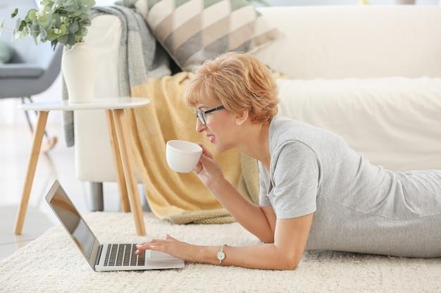 Piękna kobieta w średnim wieku z laptopem i filiżanką herbaty odpoczywa w domu