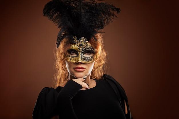 Piękna kobieta w średnim wieku z rudymi włosami w masce karnawałowej.