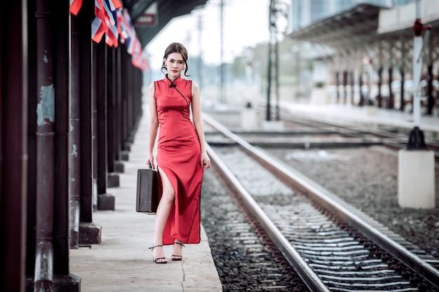 Piękna kobieta w starożytnym cheongsam oczekiwanie na pociąg na stacji kolejowej