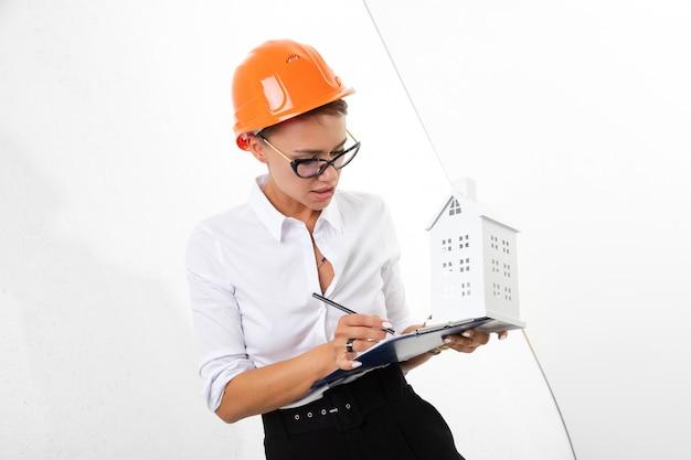 Piękna kobieta w stroju biurowym myśli o pracy, pisze notatki i trzyma pomarańczowy hełm budowlany na białym powierzchni