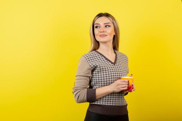 Piękna kobieta w stroju casual, trzymając filiżankę herbaty.