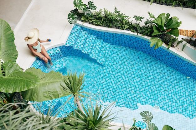 Piękna kobieta w stroju kąpielowym siedzi na brzegu basenu w słomkowym kapeluszu i pije słodki smaczny koktajl