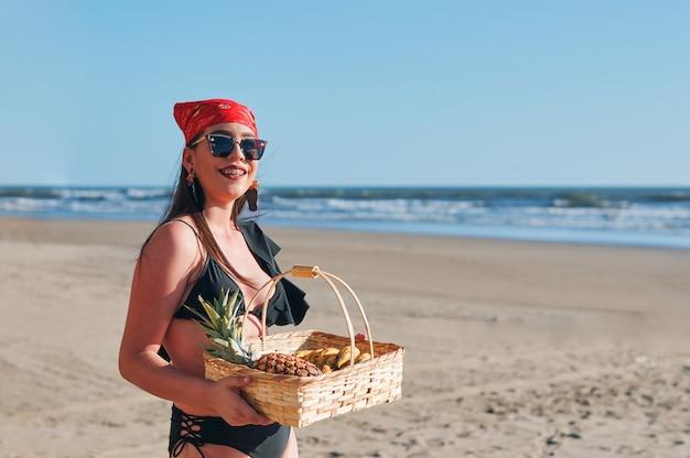 Piękna kobieta w stroju kąpielowym trzymając kosz z owocami tropikalnymi na plaży