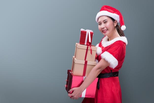 Piękna kobieta w stroju świętego mikołaja z wieloma pudełeczkami z okazji wesołych świąt i szczęśliwego nowego roku.