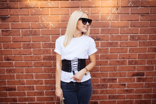 Piękna kobieta w stylową białą bluzkę pozowanie na mur z czerwonej cegły