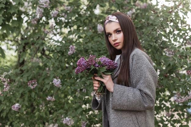 Piękna kobieta w stylowej chustce w modnej wiosennej odzieży z bukietem bzu w rękach spoczywa w pobliżu kwitnącego drzewa niesamowitego dnia wiosny na ulicy. atrakcyjna dziewczyna modelka z fioletowymi kwiatami.