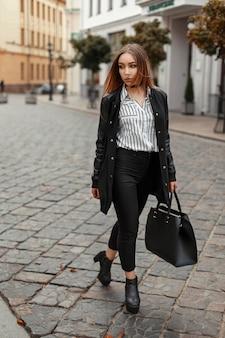Piękna kobieta w stylowym czarnym płaszczu, modne jesienne ubrania z torbą w pobliżu zabudowań w mieście