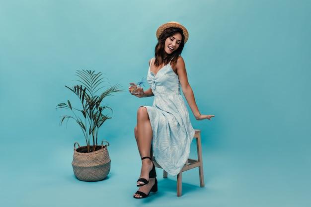 Piękna kobieta w sukience siedzi na krześle i trzyma wodę z pomarańczą na niebieskim tle