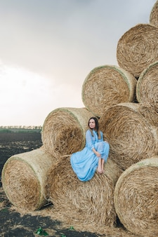 Piękna kobieta w sukni na stogach siana.