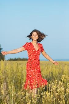 Piękna kobieta w sukni piękna śmieje się i tańczy na świeżym powietrzu na łące