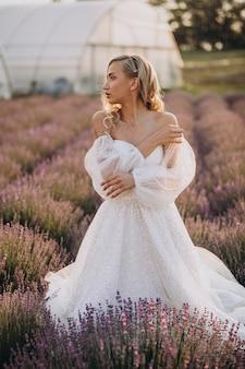 Piękna kobieta w sukni ślubnej w lawendowym polu