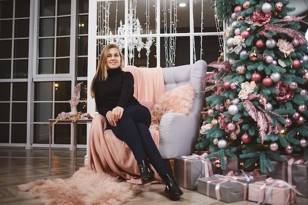 Piękna kobieta w swetrze z dzianiny siedzi na fotelu na tle luksusowo udekorowanego pokoju z choinką. dobry duch nowego roku