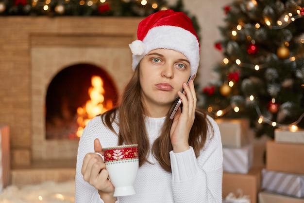 Piękna kobieta w świątecznym kapeluszu siedzi w pokoju ozdobionym choinką